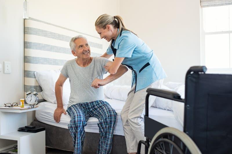 Verpleegster die oude patiënt helpen opstaan stock afbeelding