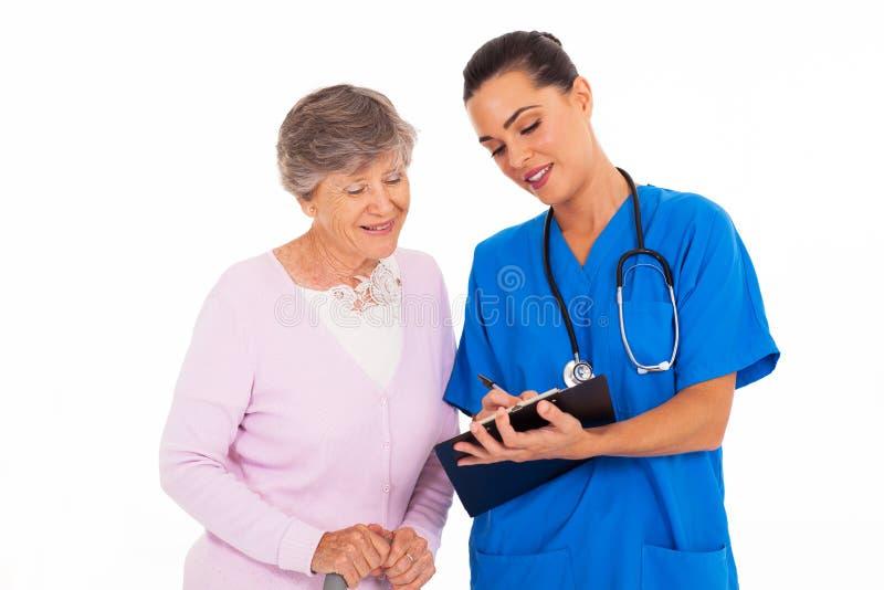 Verpleegster die oudste helpen royalty-vrije stock afbeeldingen