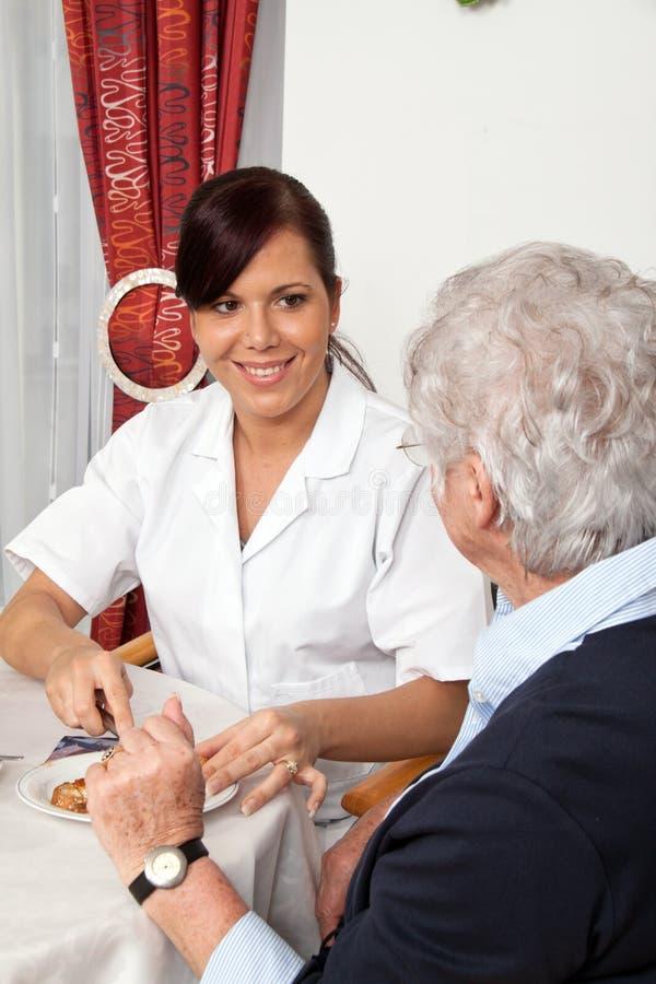 Verpleegster die oudste helpt bij ontbijt stock afbeelding