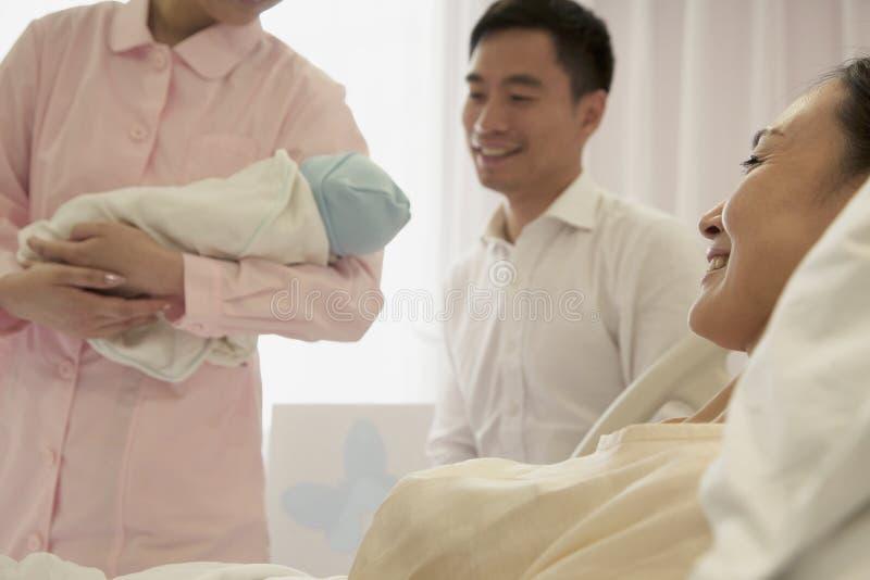 Verpleegster die pasgeboren baby in het ziekenhuis met moeder houden die op het bed en de vader naast haar liggen royalty-vrije stock foto