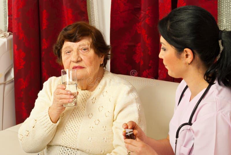Verpleegster die pillen en water geeft aan oudste stock foto
