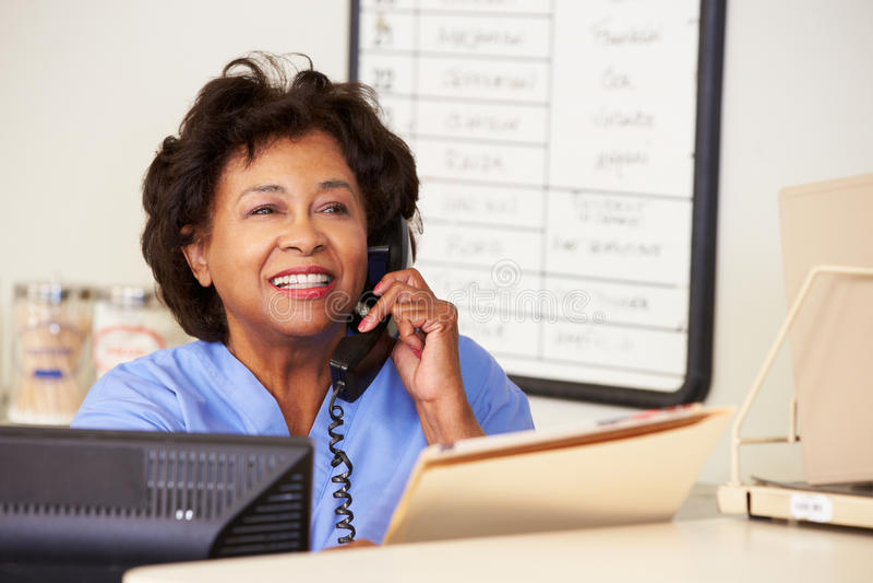 Verpleegster die Telefoongesprek maakt bij de Post van Verpleegsters royalty-vrije stock afbeelding