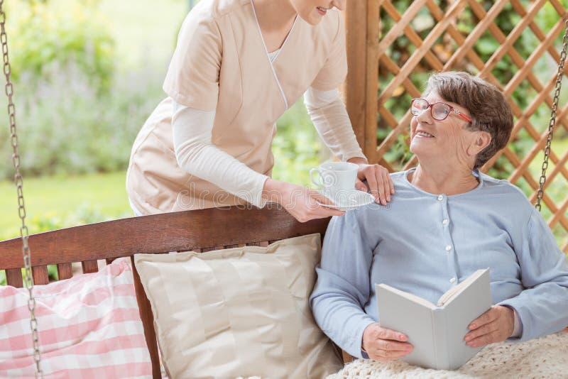 Verpleegster die thee geven aan het gelukkige boek van de bejaardelezing op terr stock afbeeldingen