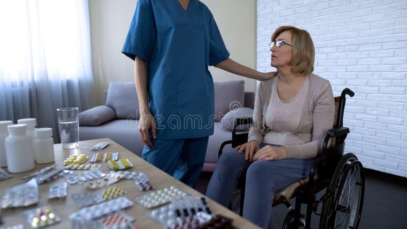Verpleegster die vermoeide vrouwelijke patiënt in rolstoel troosten, verpleeghuis, behandeling royalty-vrije stock fotografie
