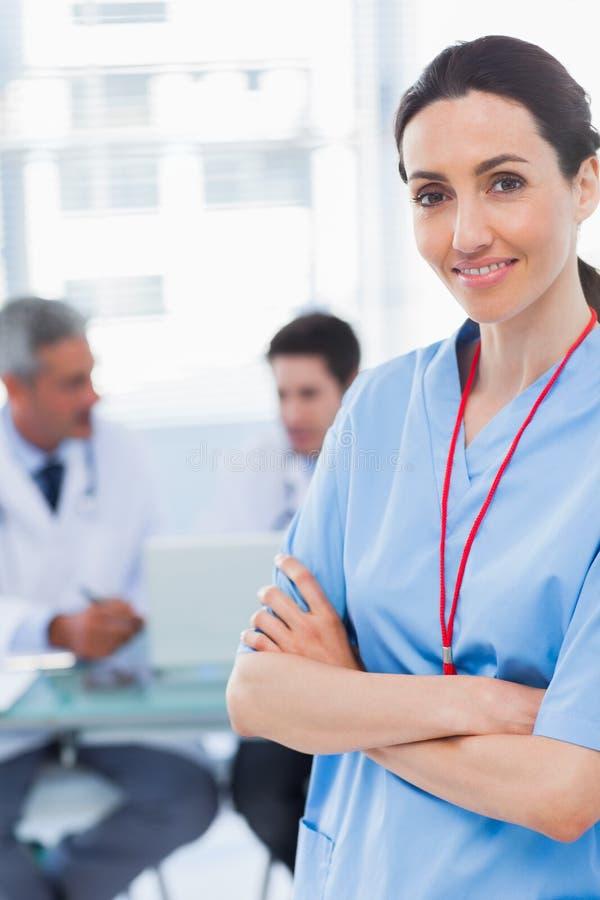 Verpleegster die wapens met haar erachter collega's kruisen stock afbeeldingen