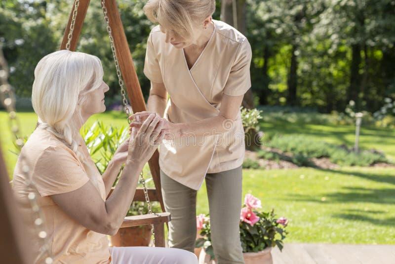 Verpleegster die water geven aan een oudste in een tuin stock afbeelding