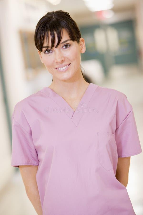 Verpleegster die zich in een Gang van het Ziekenhuis bevindt royalty-vrije stock fotografie