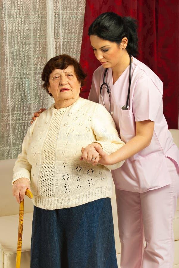 Verpleegster die ziek hoger huis helpt royalty-vrije stock foto