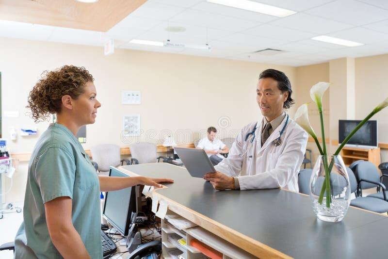 Verpleegster And Doctor Conversing bij het Ziekenhuisontvangst stock foto's