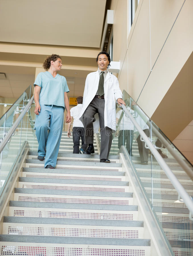 Verpleegster And Doctor Walking onderaan Treden in het Ziekenhuis stock afbeeldingen