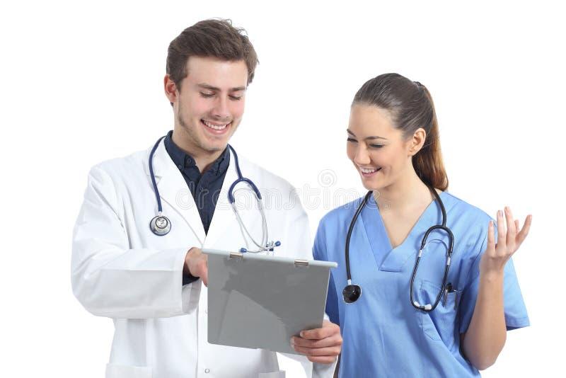Verpleegster en arts die medische geïsoleerde geschiedenis raadplegen over wit stock afbeelding