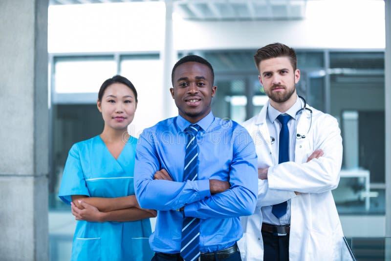 Verpleegster en arts met zakenman status in het ziekenhuis stock afbeelding
