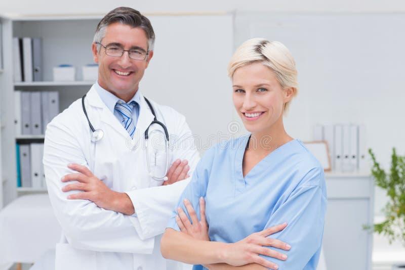 Verpleegster en artsen bevindende die wapens bij kliniek worden gekruist royalty-vrije stock foto