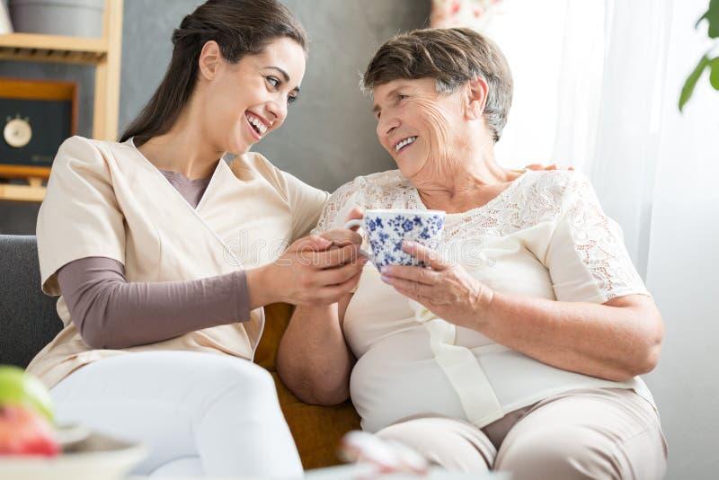 Verpleegster en het bejaarde dame lachen stock foto's