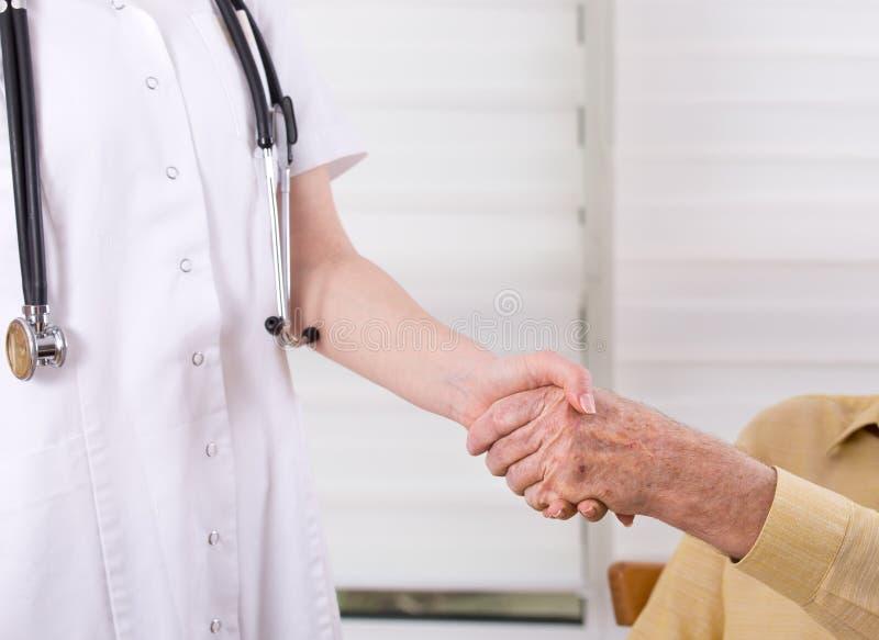Verpleegster en hogere mens het schudden handen stock afbeeldingen
