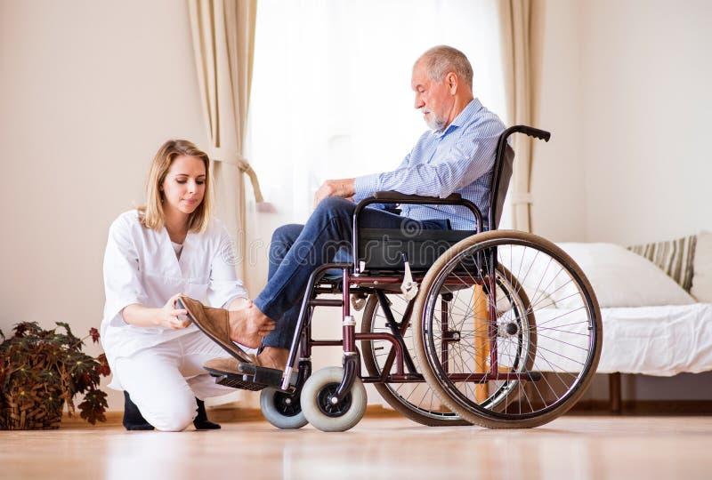 Verpleegster en hogere mens in rolstoel tijdens huisbezoek stock afbeelding