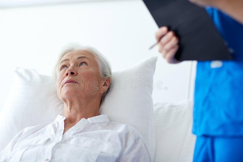 Verpleegster en hogere vrouwenpatiënt bij het ziekenhuis stock afbeelding