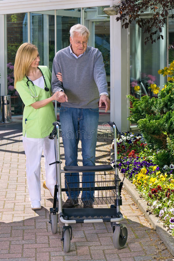 Verpleegster Helping Senior Man met Walker Outdoors stock fotografie