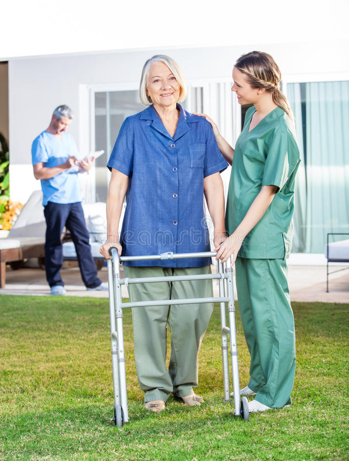 Verpleegster Helping Senior Woman aan Gebruik het Lopen Kader binnen royalty-vrije stock afbeelding