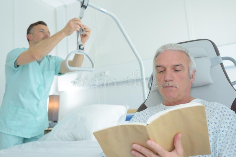 Verpleegster het aanpassen boek van de hijstoestel het geduldige lezing royalty-vrije stock afbeeldingen