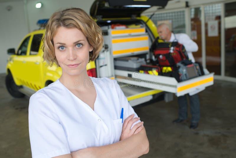Verpleegster het stellen naast medische auto royalty-vrije stock fotografie