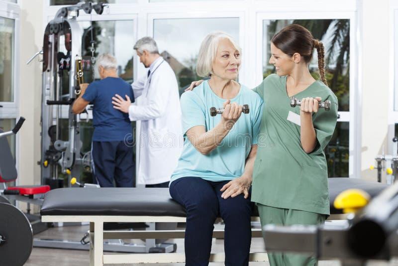 Verpleegster Instructing Senior Patient die met Domoor uitoefenen stock afbeelding