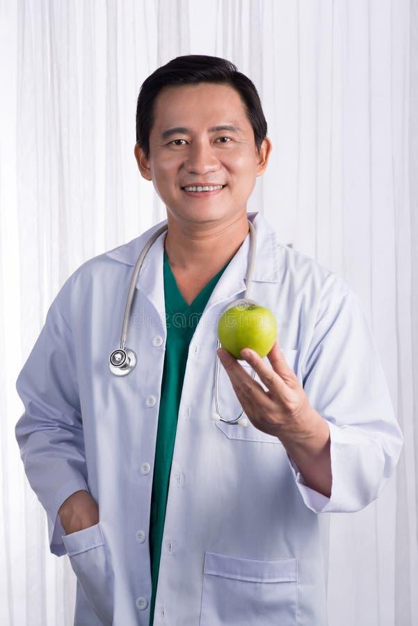 Verpleegster of mannelijke arts die appel het glimlachen geven Gezondheidszorgconcept op witte achtergrond royalty-vrije stock foto