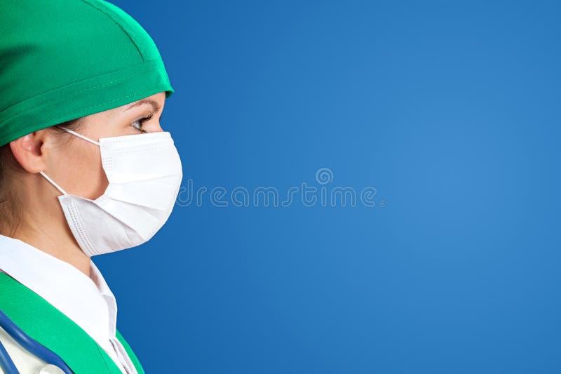 Verpleegster in masker met blauwe achtergrond stock foto's