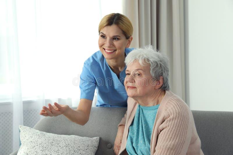 Verpleegster met Bejaarde Bijwonende hogere mensen royalty-vrije stock afbeelding