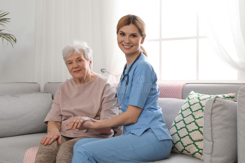 Verpleegster met Bejaarde Bijwonende hogere mensen stock afbeeldingen