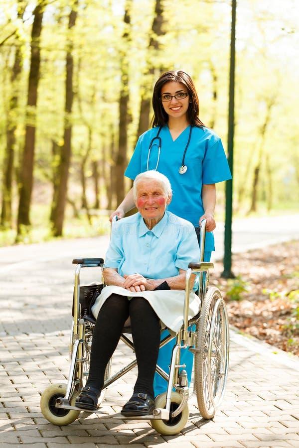 Verpleegster met bejaarde Dame in Rolstoel royalty-vrije stock afbeelding