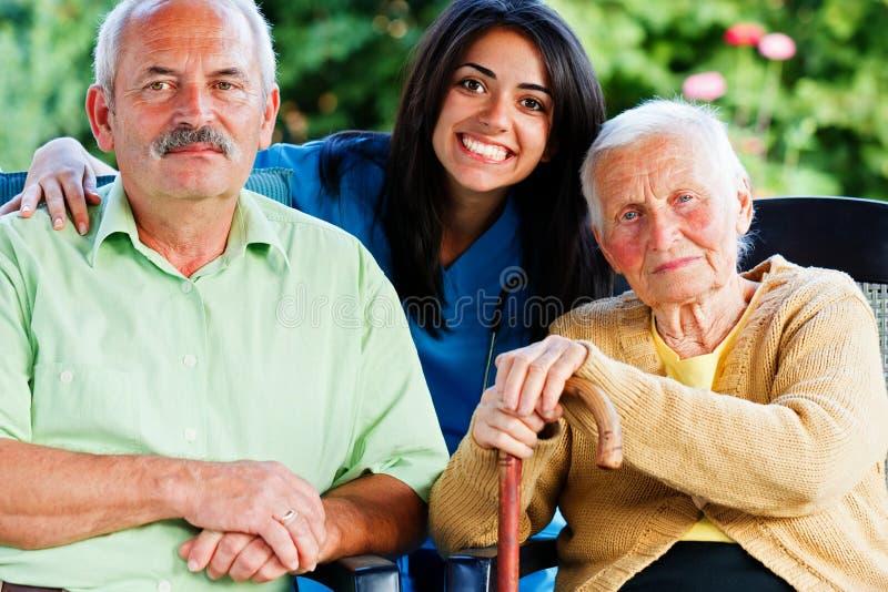 Verpleegster met Bejaarde Mensen stock afbeelding