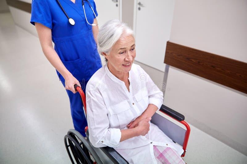 Verpleegster met hogere vrouw in rolstoel bij het ziekenhuis stock foto's