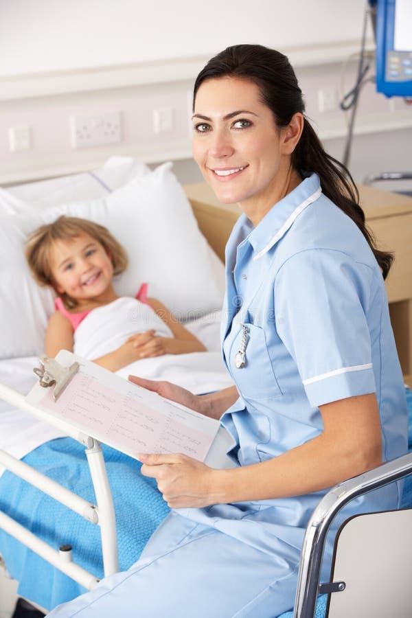 Verpleegster met kind in het Britse ziekenhuis stock afbeelding