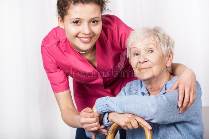 Verpleegster met zittingsbejaarde royalty-vrije stock foto's