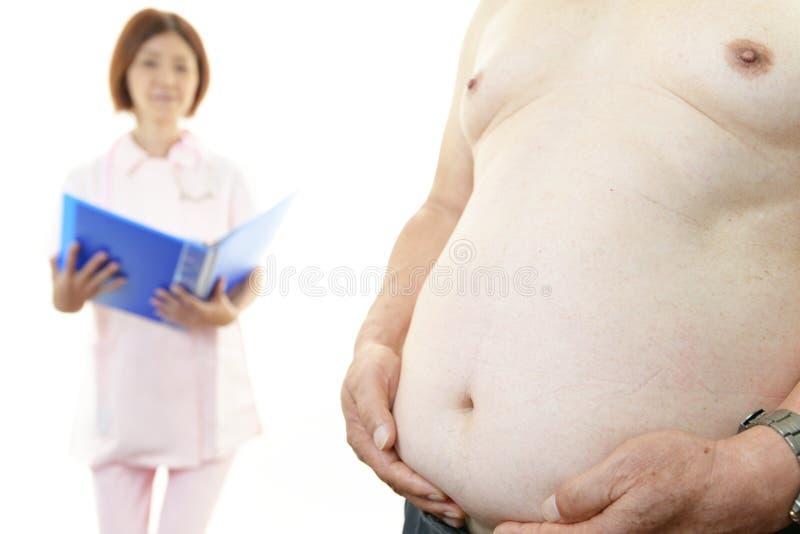 Verpleegster met zwaarlijvige patiënt stock fotografie