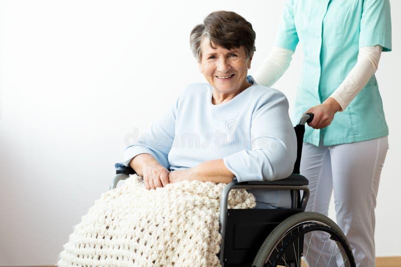 Verpleegster ondersteunend gelukkige gehandicapte hogere vrouw in een rolstoel royalty-vrije stock afbeelding