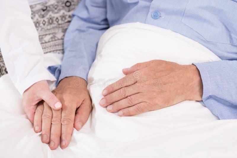 Verpleegster ondersteunend oude mannelijke patiënt royalty-vrije stock afbeelding