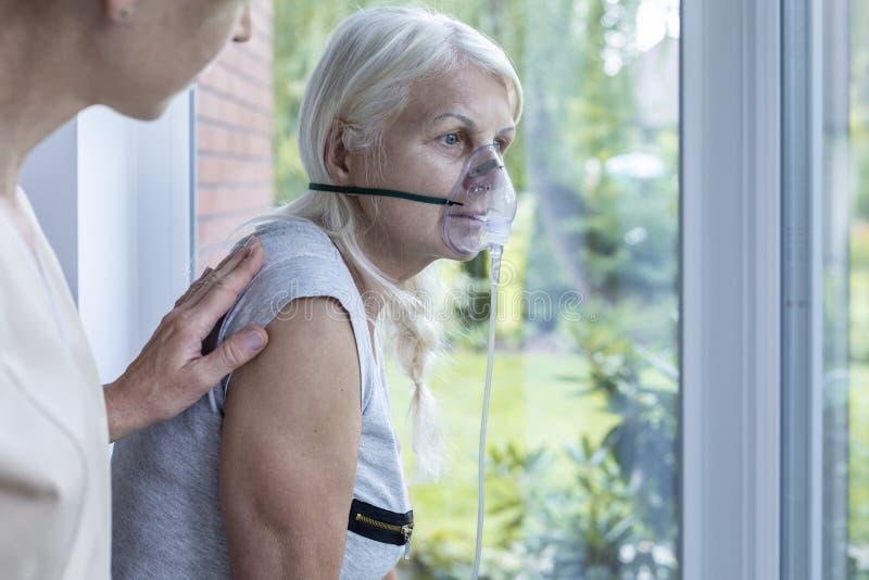 Verpleegster ondersteunend zieke hogere vrouw met zuurstofmasker stock fotografie