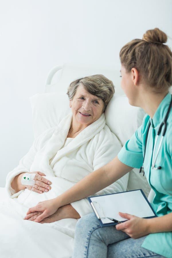 Verpleegster ondersteunend zieke vrouw stock foto's