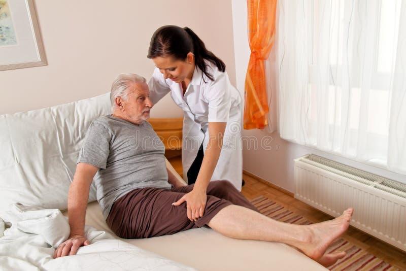 Verpleegster in oude zorg voor de bejaarden stock afbeelding