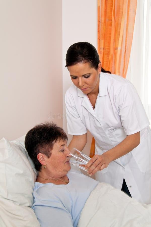 Verpleegster in oude zorg voor de bejaarden stock fotografie
