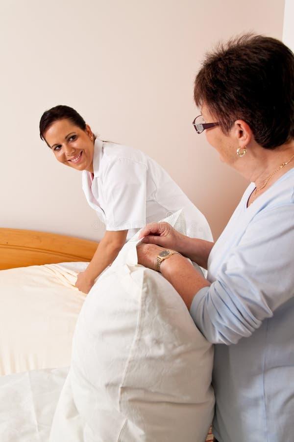 Verpleegster in oude zorg voor de bejaarden in verzorging stock foto's