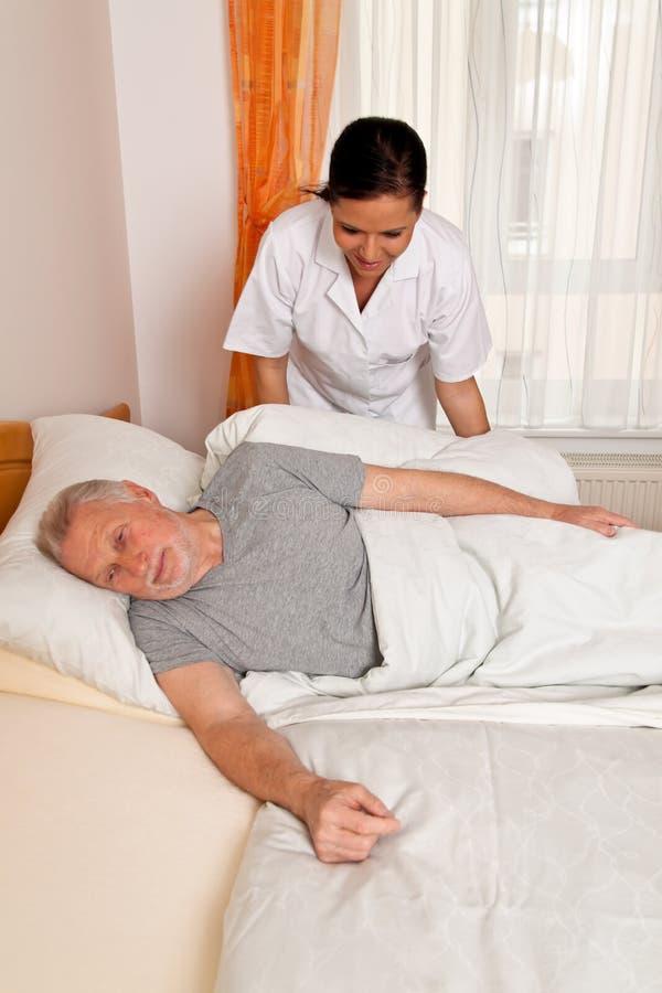 Verpleegster in oude zorg voor de bejaarden in verzorging stock fotografie