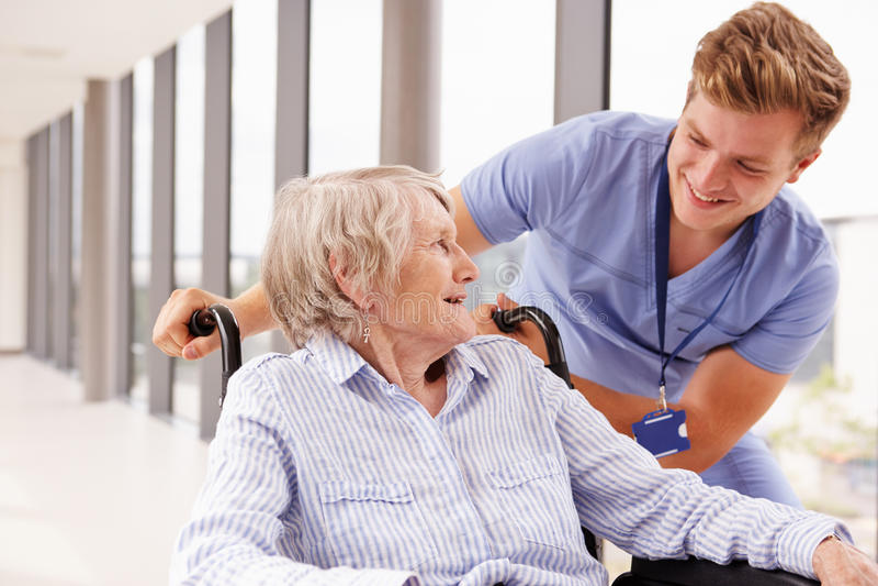 Verpleegster Pushing Senior Patient in Rolstoel langs Gang royalty-vrije stock fotografie