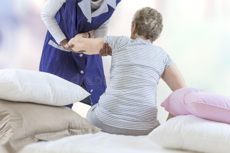 Verpleegster in verpleeghuis die het hogere vrouw opstaan van bed in haar slaapkamer bevorderen stock foto's