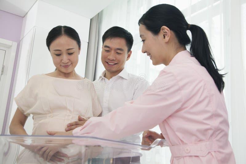 Verpleegster wat betreft de buik van de zwangere vrouw in het ziekenhuis met echtgenoot naast haar royalty-vrije stock afbeeldingen