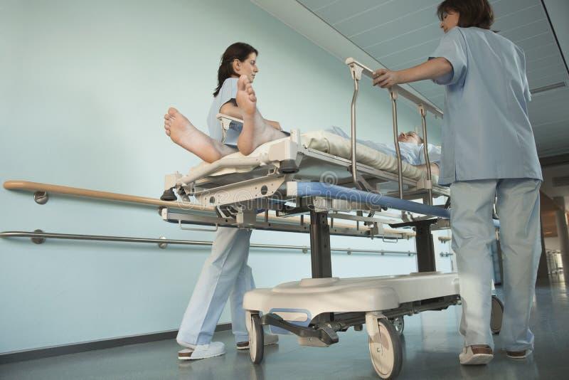 Verpleegsters die Patiënt op Gurney in het Ziekenhuisgang bewegen stock afbeeldingen