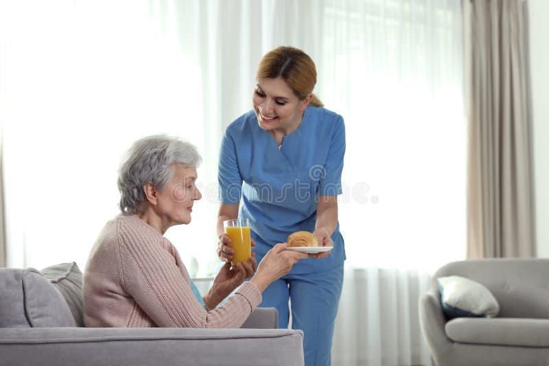 Verpleegsters dienend ontbijt aan bejaarde binnen Bijwonende hogere mensen stock foto's