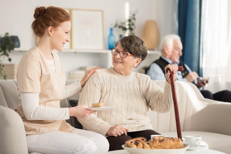 Verpleegsters dienende cake voor gepensioneerde stock foto